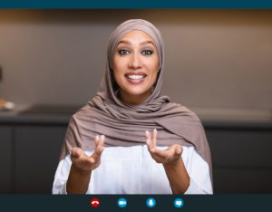 A photo of a woman in a headscarf speaking and gesturing on a computer screen during a video call, demonstrating a video interview tip: maintaining good posture throughout the virtual interview.