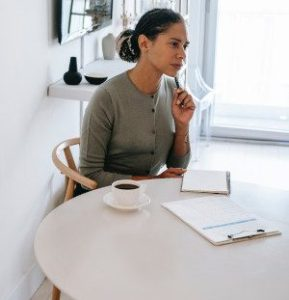 A photo of a woman with a clipboard and notebook and a skeptical expression, illustrating that some hiring managers are skeptical of pain letters as they find them arrogant.