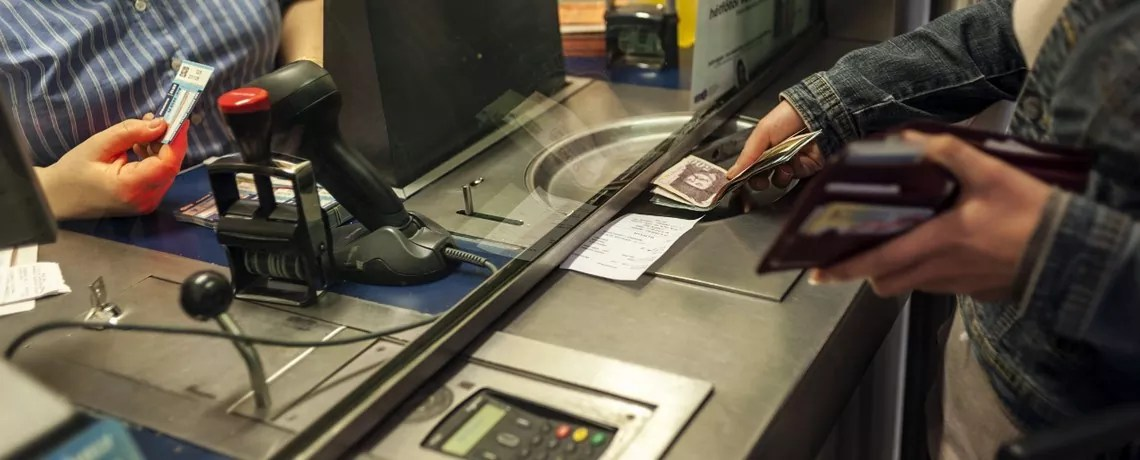 Buying a monthly transportation pass from a cashier