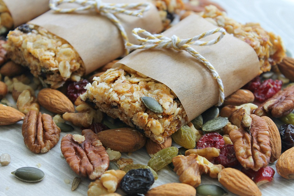 Healthy granola oat bars wrapped in brown paper and tied with string, sitting on a bed of nuts and seeds