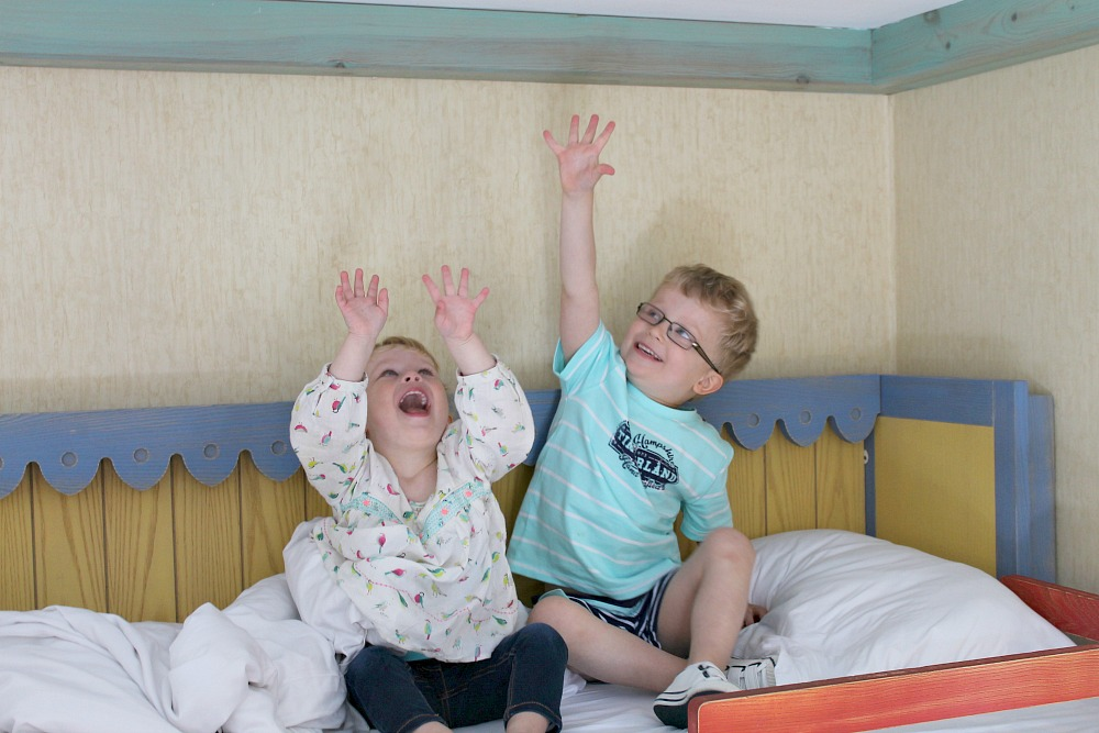 A young boy and girl sitting on the top bunk of a bed with their arms stretched above their heads, reaching for the roof