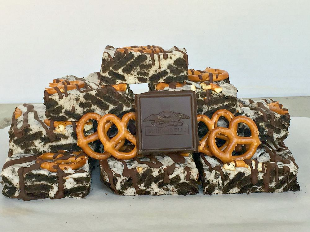 A tower ofSalted Oreo Cookie Bars with 4 pretzles and a square of chocolate balanced on them