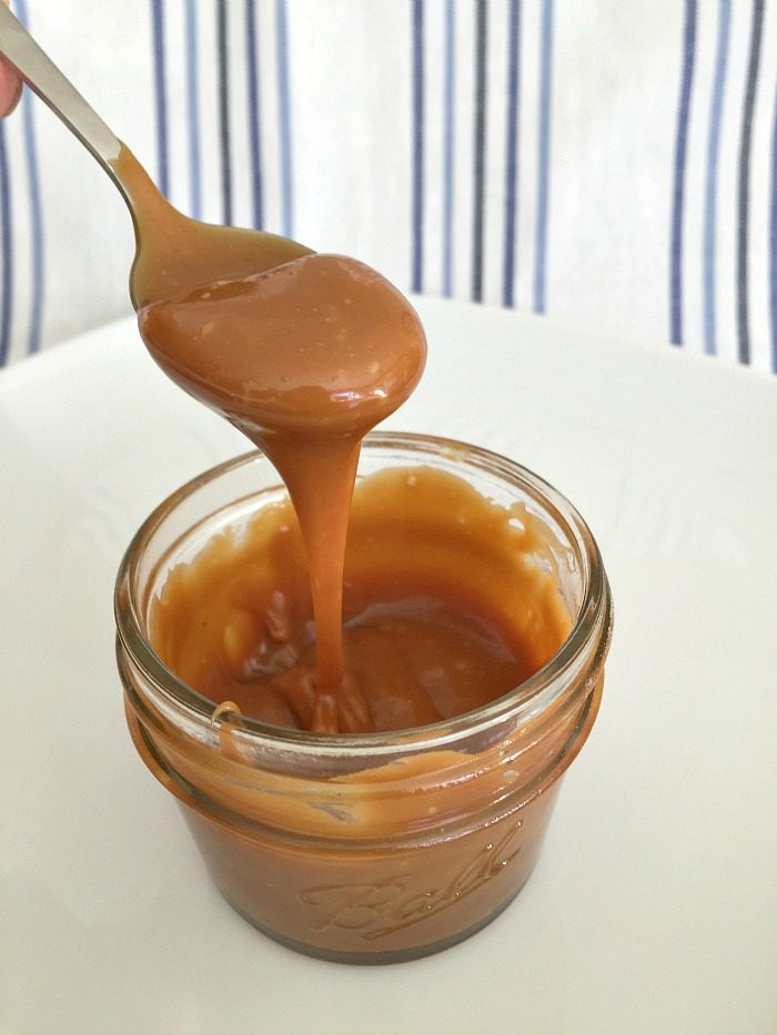 A jar of salted caramel sauce, with a spoon lifting some out and letting it drip back into the jar