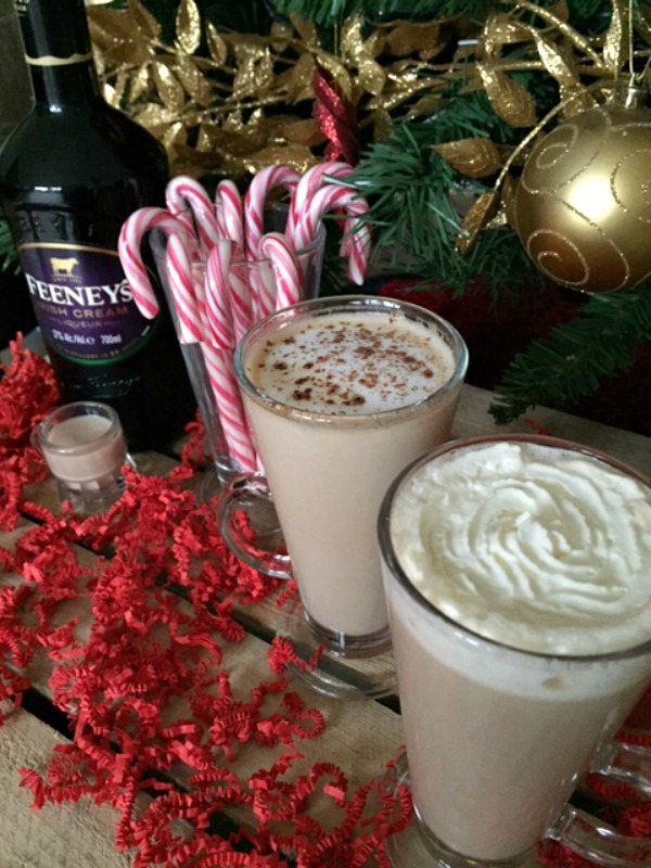 A bottle of Irish cream standing next to a mug of candy canes and 2 coffees