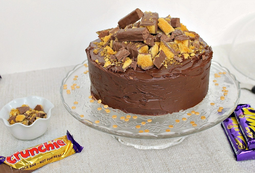 A chocolate cake with crunchie and twirl on top, sitting on a glass cake stand