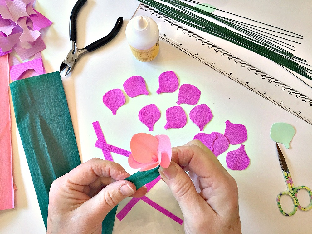 Tools for creating paper flowers. Crepe paper petals, a ruler and scissors on a table