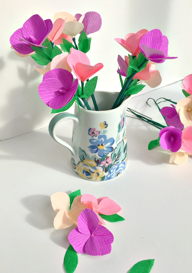 A jug willed with crepe paper flowers in pink and purples