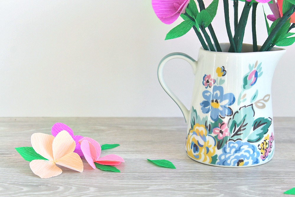 A jug decorated with flowers, and a few crepe paper flowers next to it