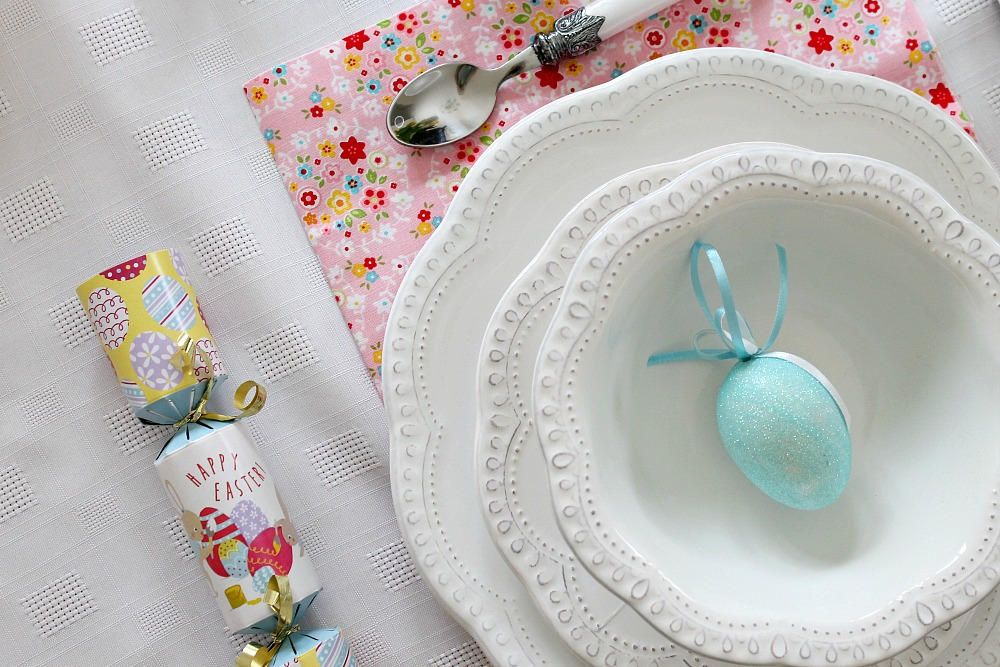 A white crockery set with a floral napkin, blue decorative egg and Easter cracker