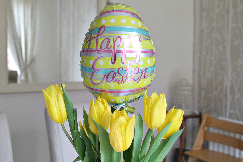 "A bunch of yellow tulips with an egg shaped balloon with ""Happy Easter"" coming out the top"