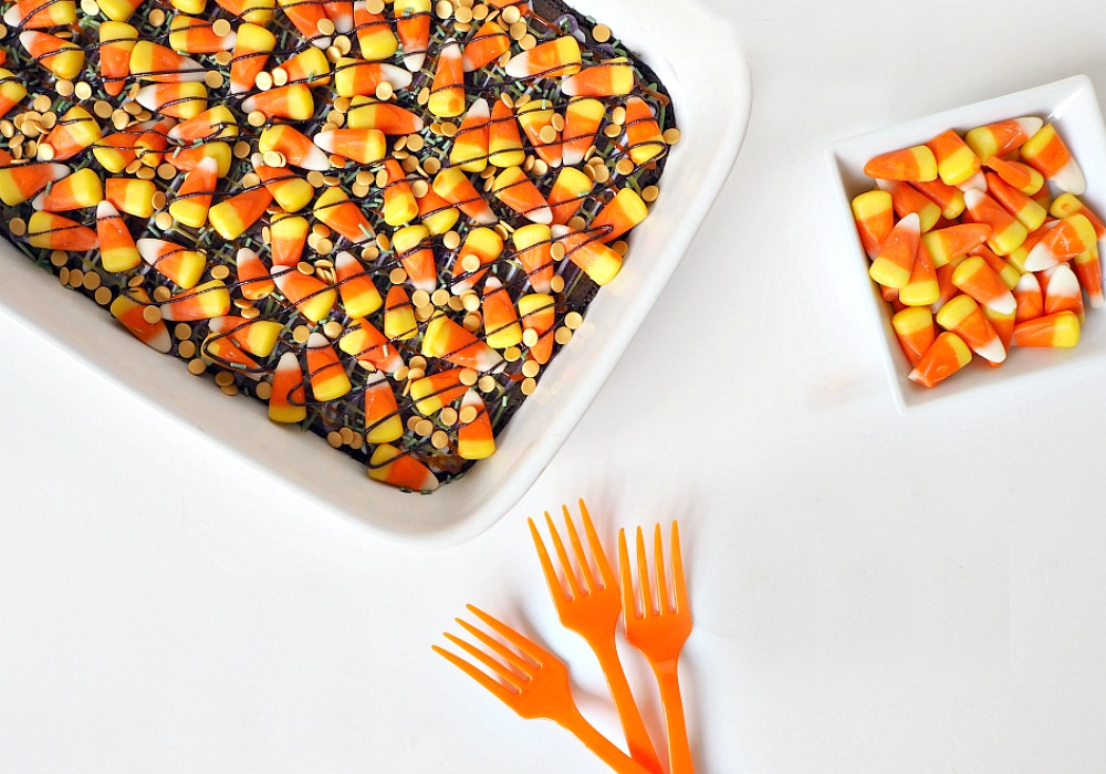 A tray of Halloween Brownies , with 3 orange forks and a bowl of candy corn