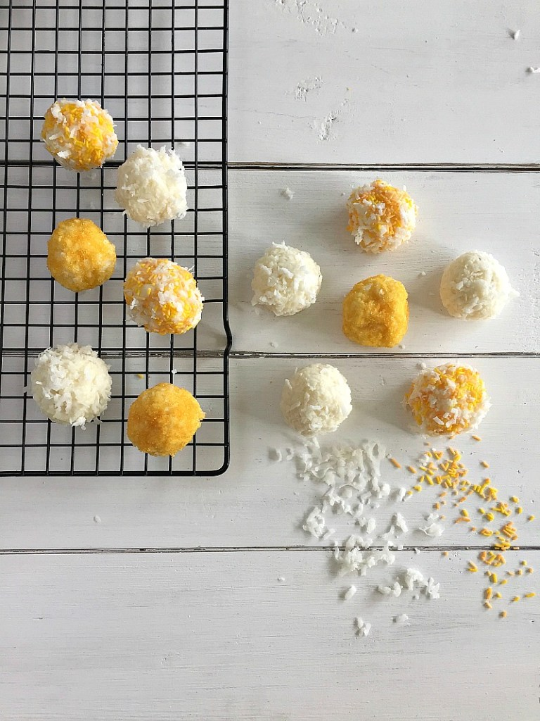 Some orange and white snowballs on a cooling rack. Yellow sprinkles and coconut shavings surround them.