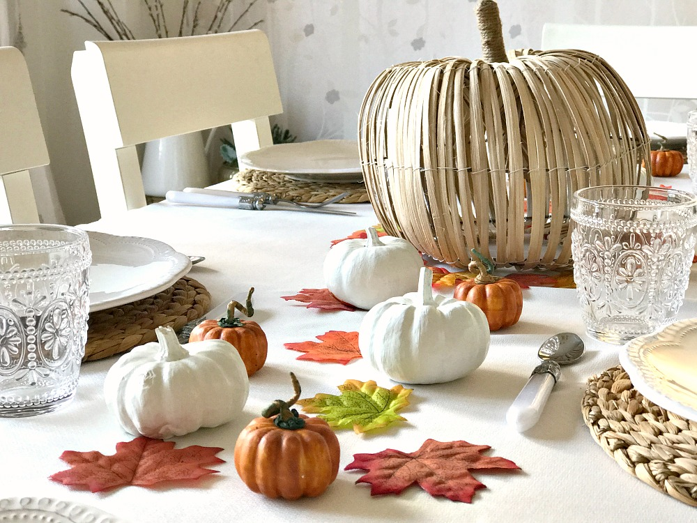 A table decorated for Thanksgiving with fake leaves, orange and white pumpkins and a large wicker pumpkin alongside plates and cutlery