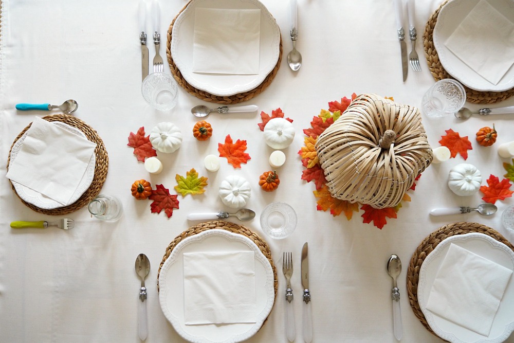 A Thanksgiving tablescape with pumpkins and leaves