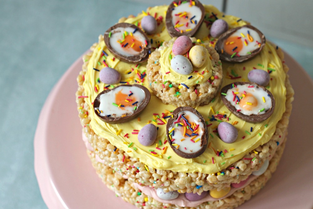 An Easter cake make out of rice crispy treats sits on a pink cake stand, topped with mini eggs and creme eggs