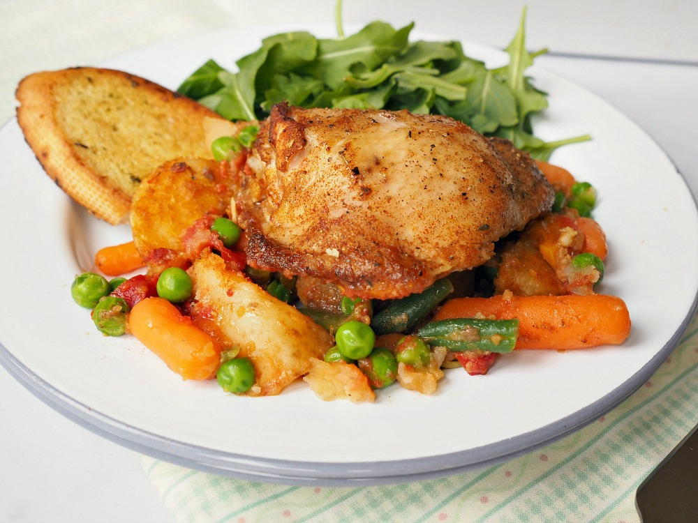 A plate with Chicken, mixed vegetables, garlic bread and a leaf salad.