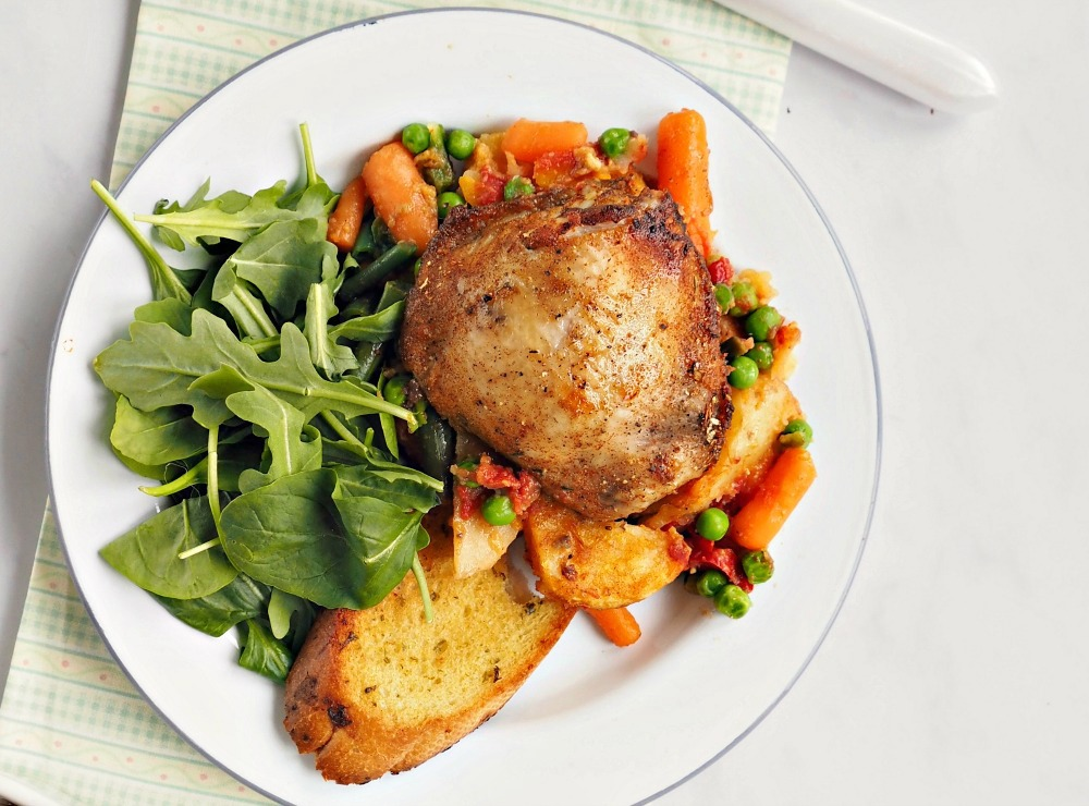 A plate with Rustic Chicken Casserole, mixed vegetables, garlic bread and a leaf salad.