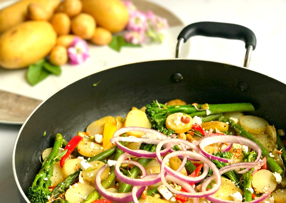 A frying pan containing Lime and Chilli Potatoes with onion, peppers and tenderstem broccoli. In the background is a pile of potatoes and pink flowers.
