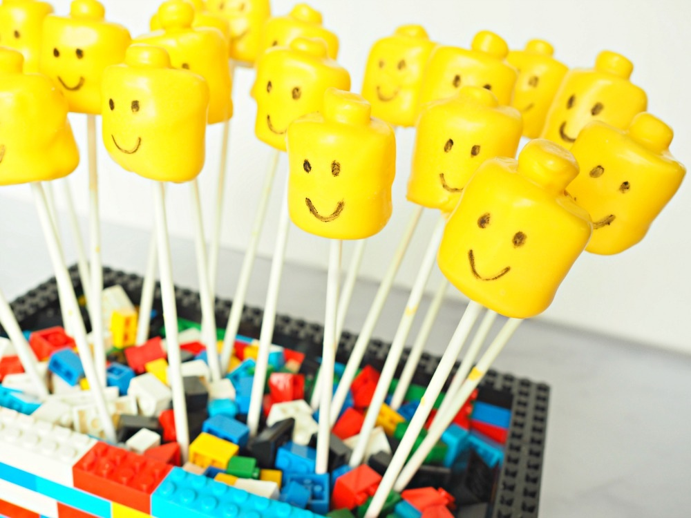 yellow Lego marshmallow pops in a base made out of multicoloured lego bricks