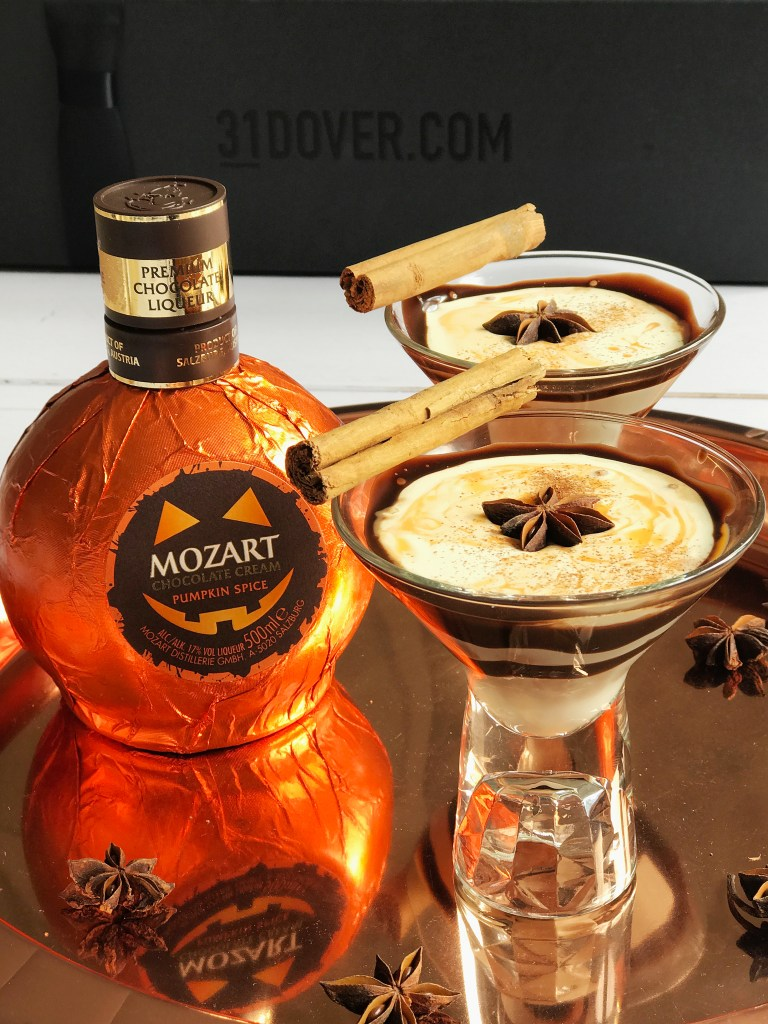 A bottle of chocolate cream pumpkin spice liqueur next to 2 chocolate pumpkin spice martini cocktails with a star anise and a cinnamon stick on top, sitting on a copper tray