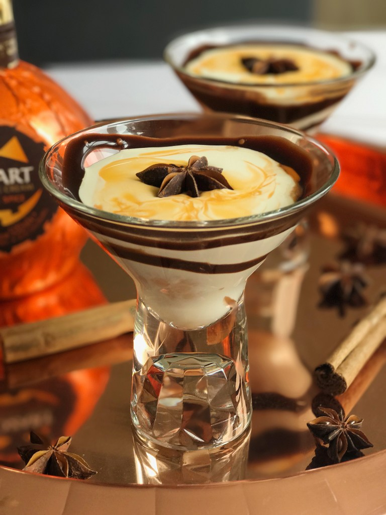 2 chocolate pumpkin spice martini cocktails with a star anise and a cinnamon stick on top, sitting on a copper tray