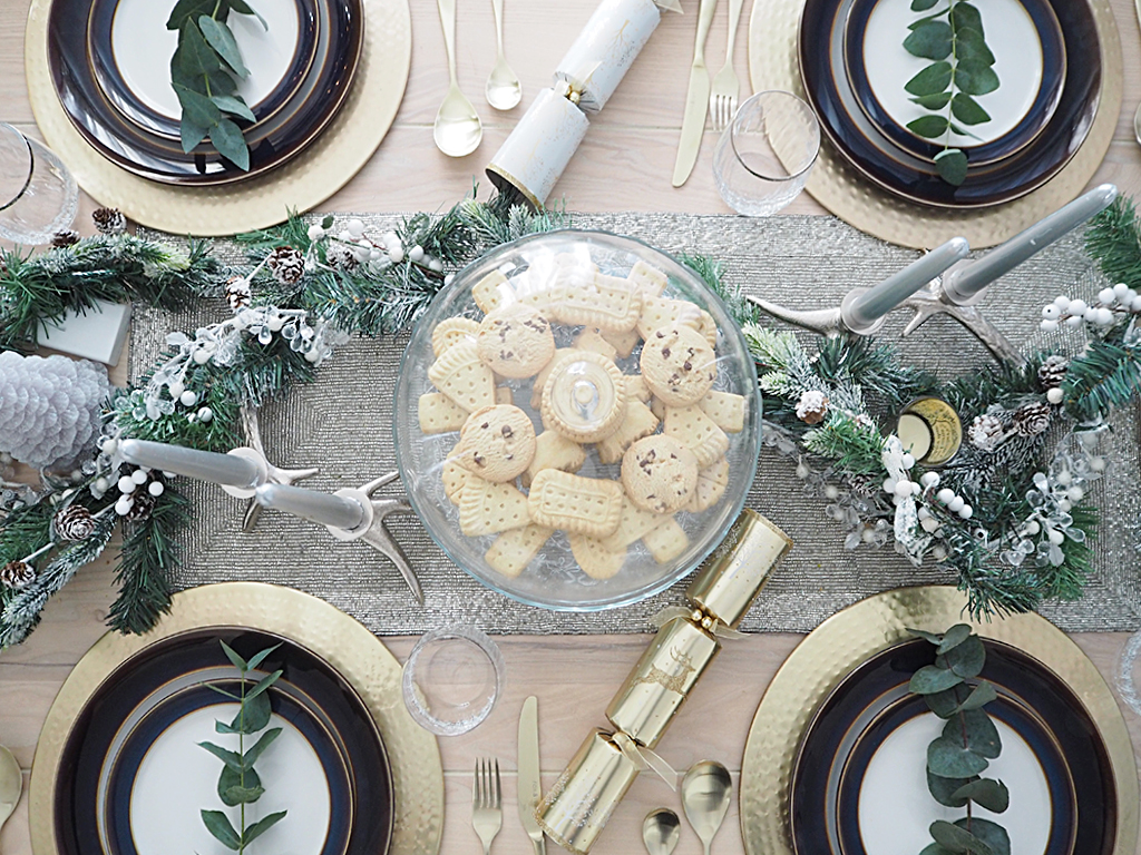 A rustic Christmas table centrepiece. A dish of cookies is in the middle of the table, surrounded my a Christmas garland and 4 table settings