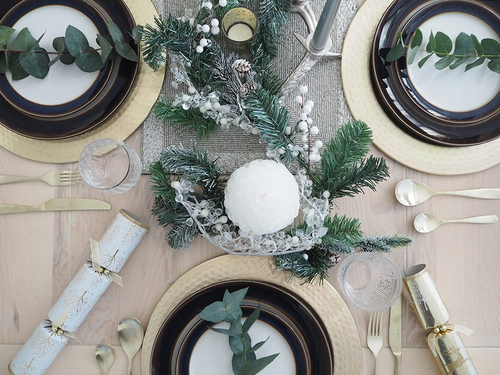 A rustic Christmas table decoration with candles, a Christmas garland, white and gold crackers and gold cutlery