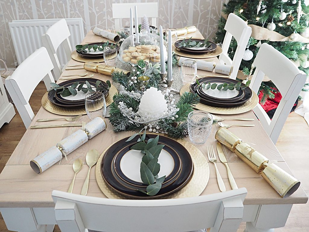 A table set for Christmas dinner in a rustic theme with gold and white accents