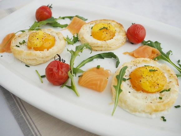A plate of baked eggs, smoked salmon, rocket and roasted cherry tomatoes