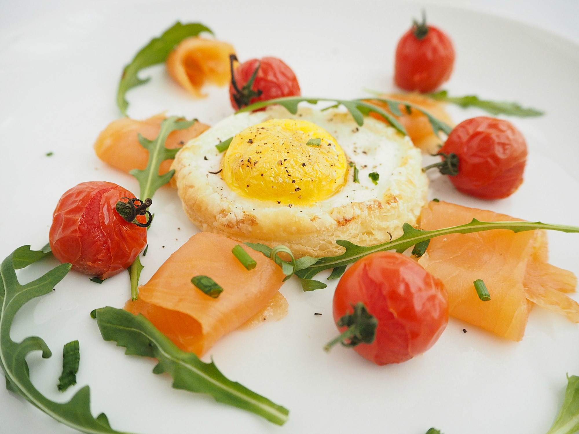 A plate of baked eggs in a cheesy pastry, smoked salmon, rocket and roasted cherry tomatoes