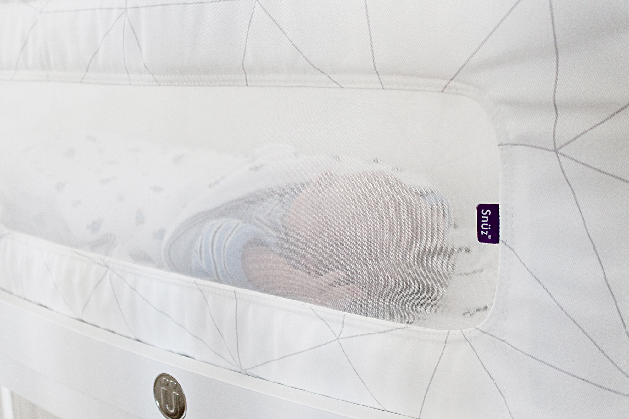 View of the side of a SnuzPod co-sleeper where a baby can be seen asleep in it through the mesh side