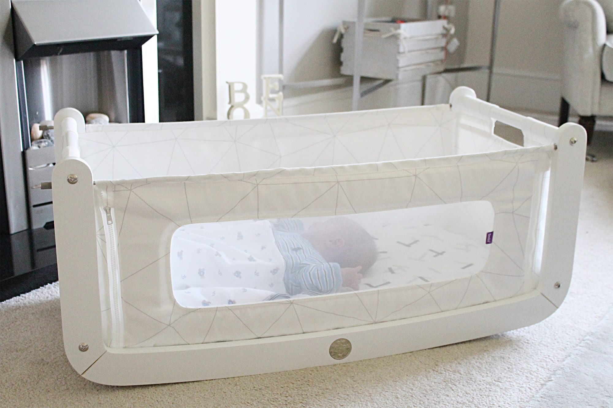 A white rocking bassinet on the floor of a living room