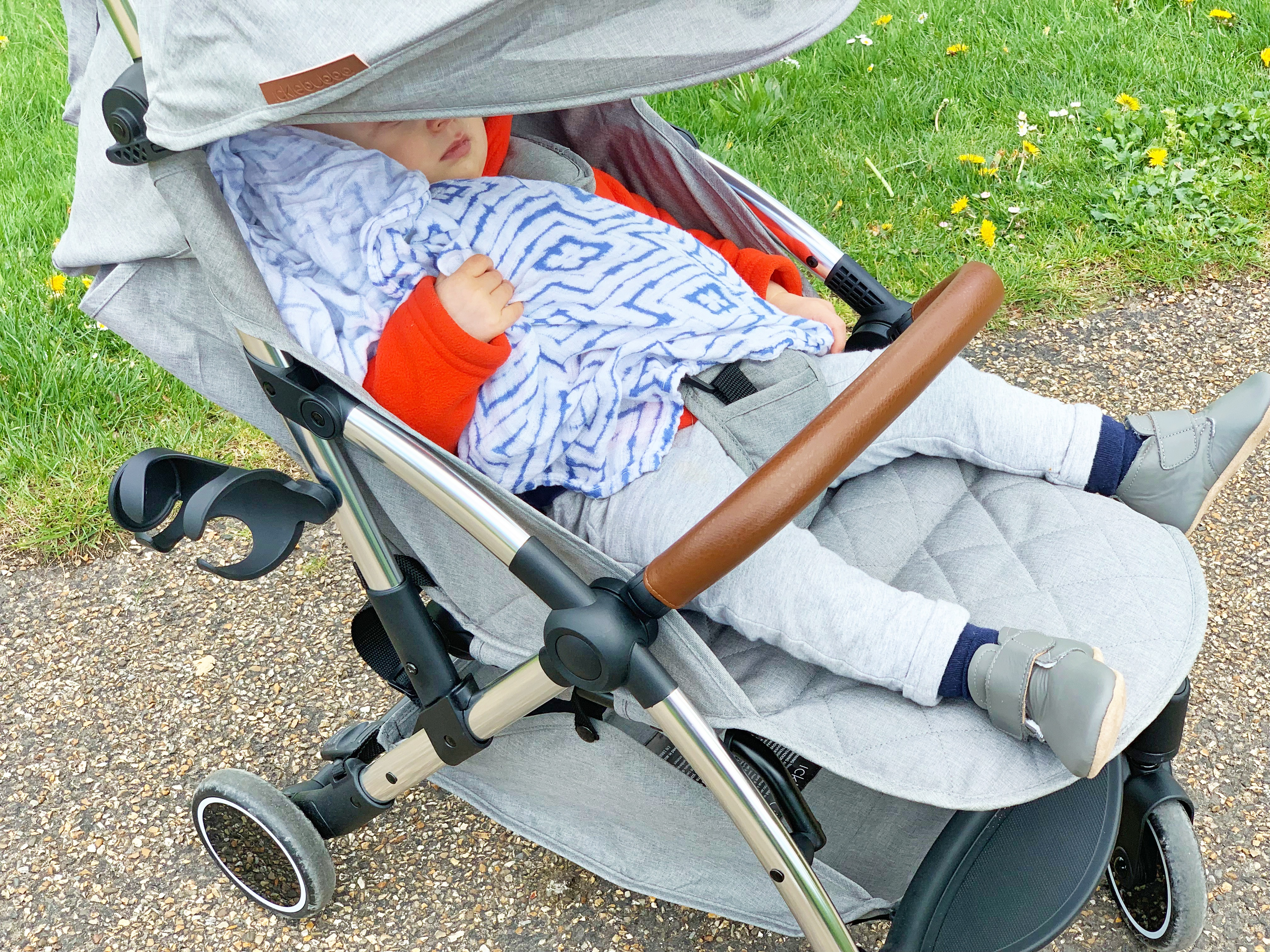 A baby sleeping in a grey Ickle Bubba's compact travel stroller