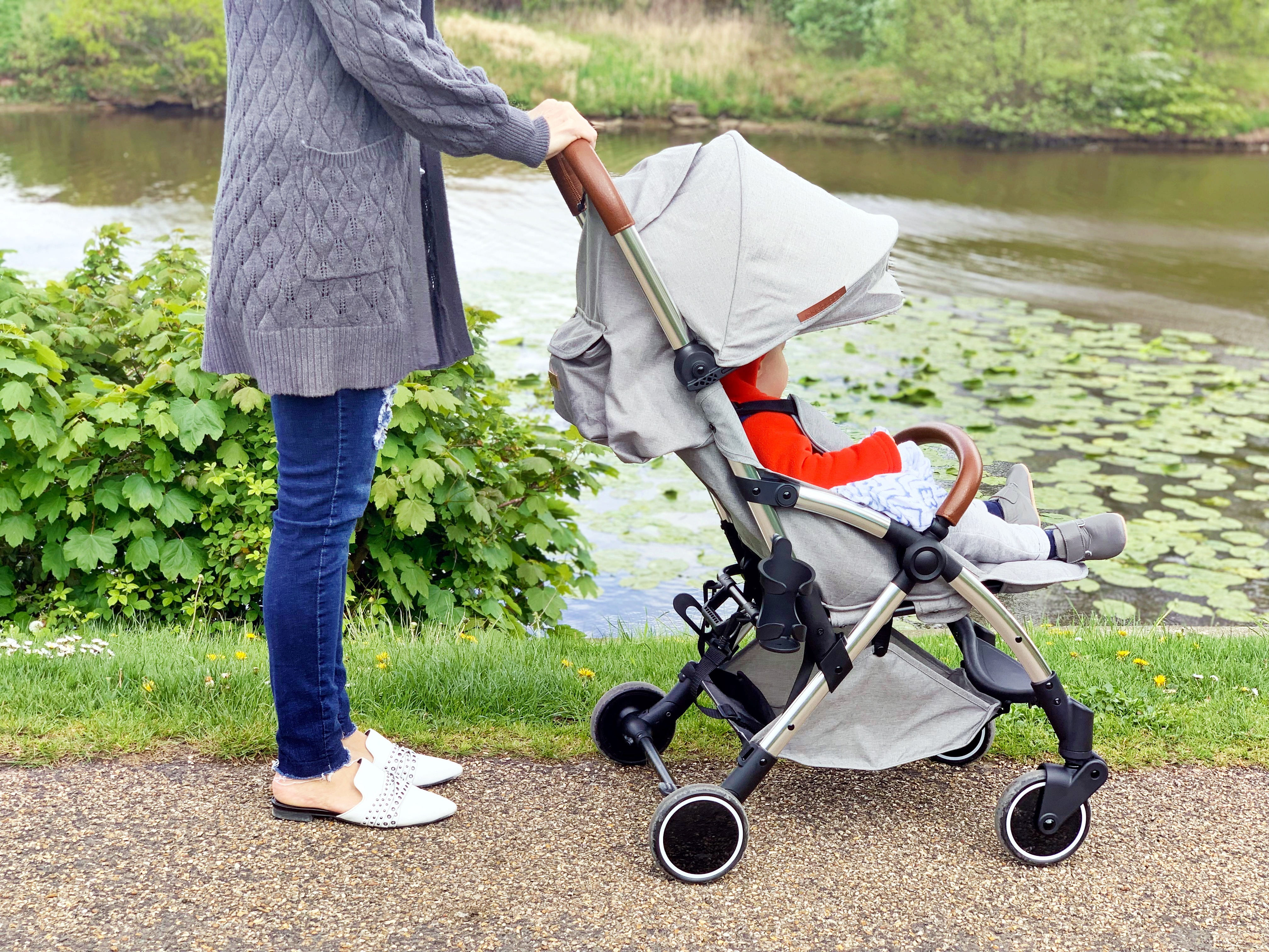 A woman pushing a grey pram next to a lake with a toddler sitting in it