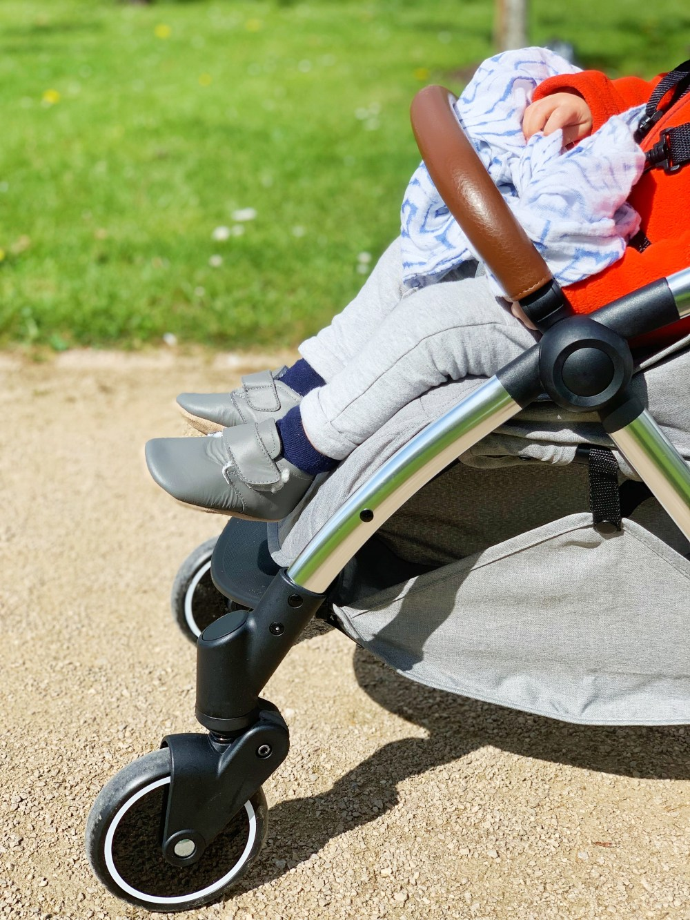 A child's legs and feet as they sit in a stroller in the park