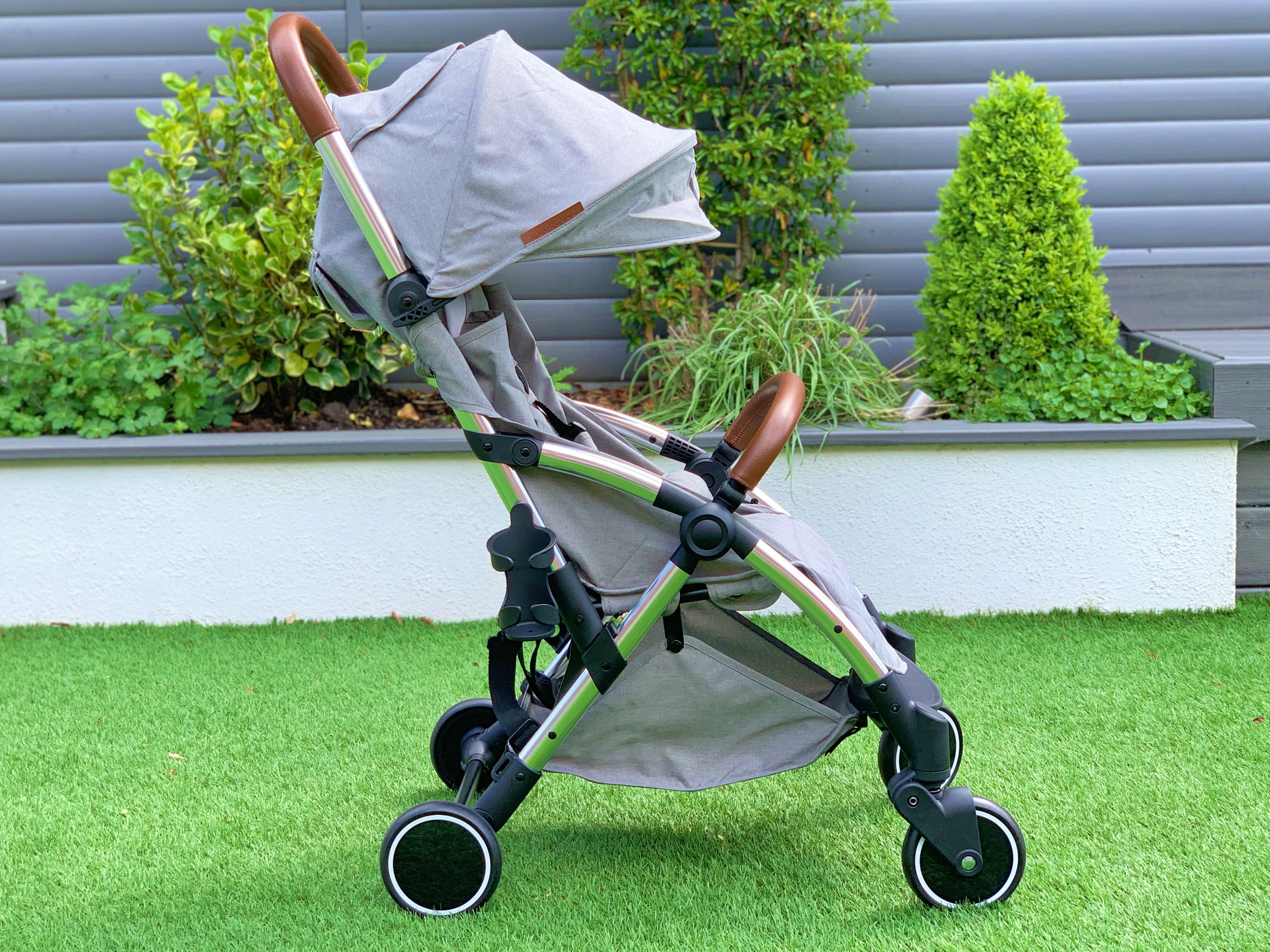 A grey pushchair with brown leather on the handle on bumper bar. It is on some grass with a raised bed behind it.