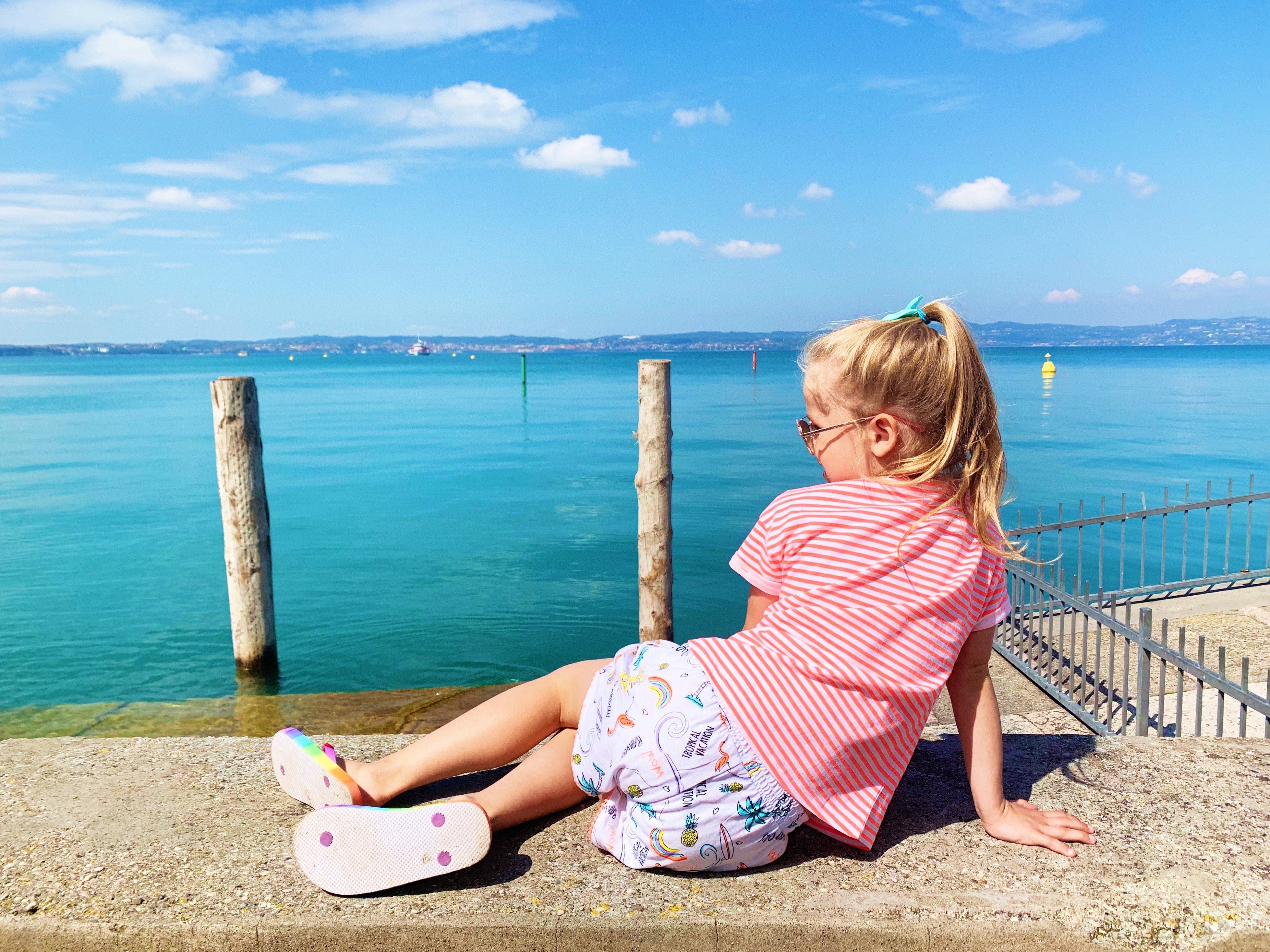 A young girl poses next to a lake in Sirmione Italy