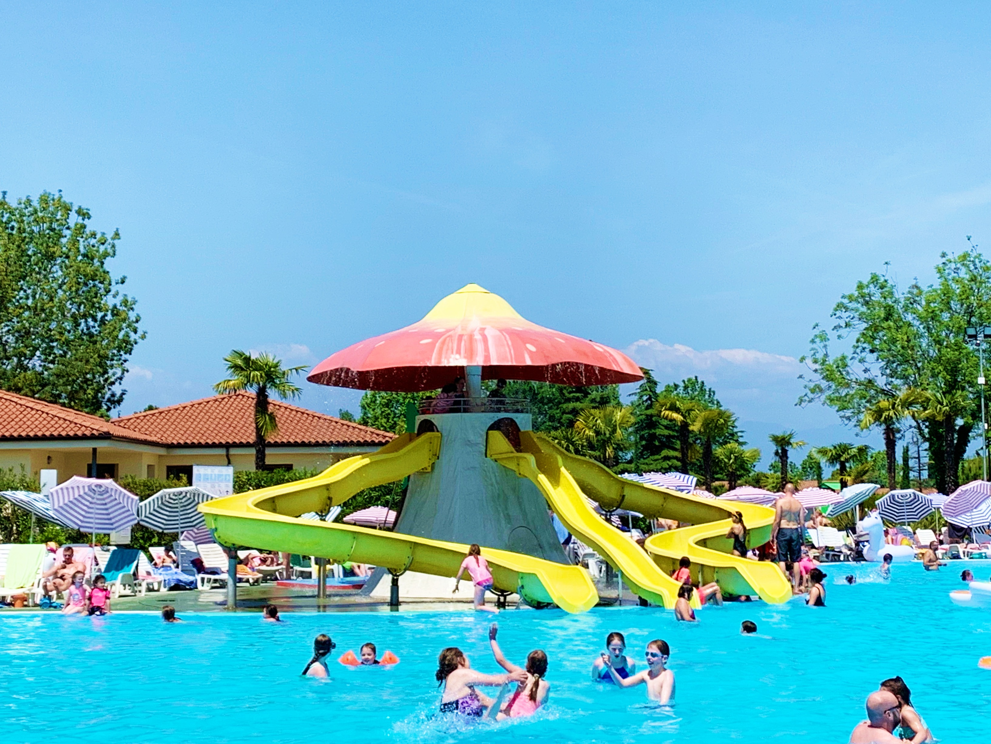 A swimming pool with yellow slides going in to it in Eurocamp Bella Italia on Lake Garda