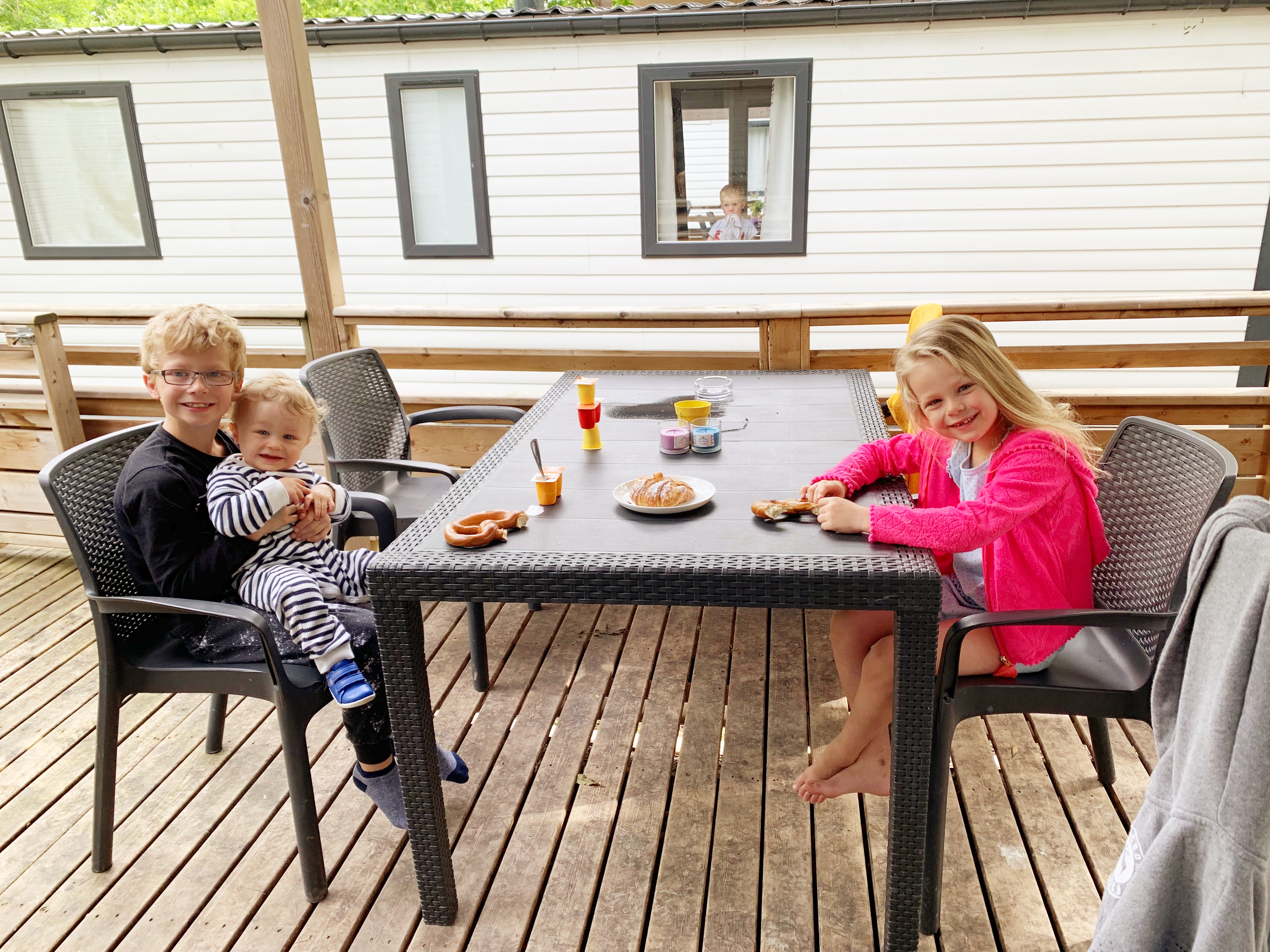 A table and chairs on a deck outside a Eurocamp Avant lodge. The table is set with some kids snacks, and a boy sits on the left with his younger brother on his knee. A girl sits on the other side of the table. All 3 children are smiling at the camera.