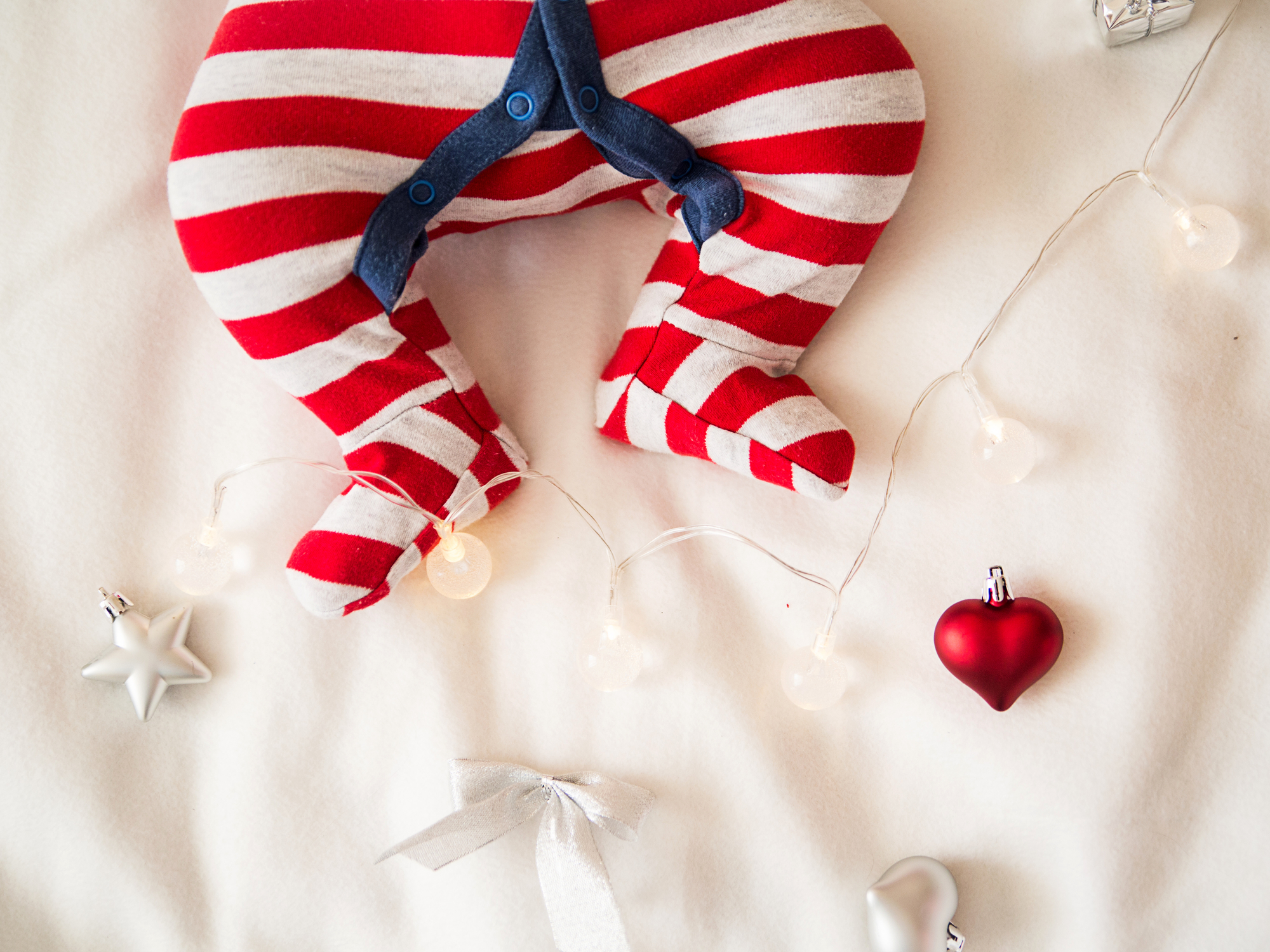 A baby in a red and white striped onesie with it's feet next to some Christmas lights and baubles