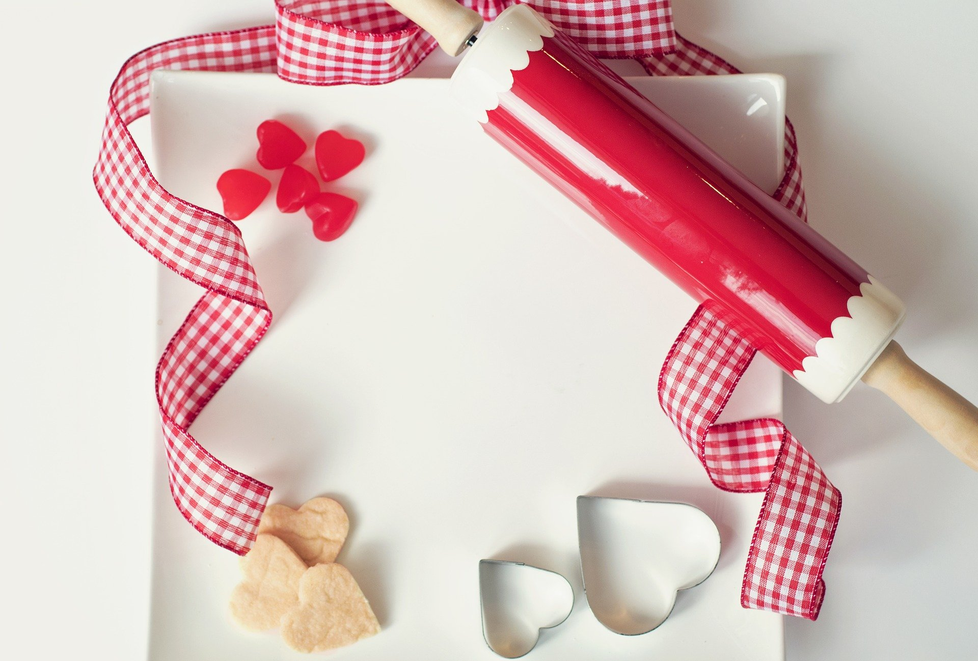 A red and white gingham ribbon on a plate, with a red and white rolling pin, heart shaped sweets, 2 heart cookie cutters and 3 hearts shaped cookies.