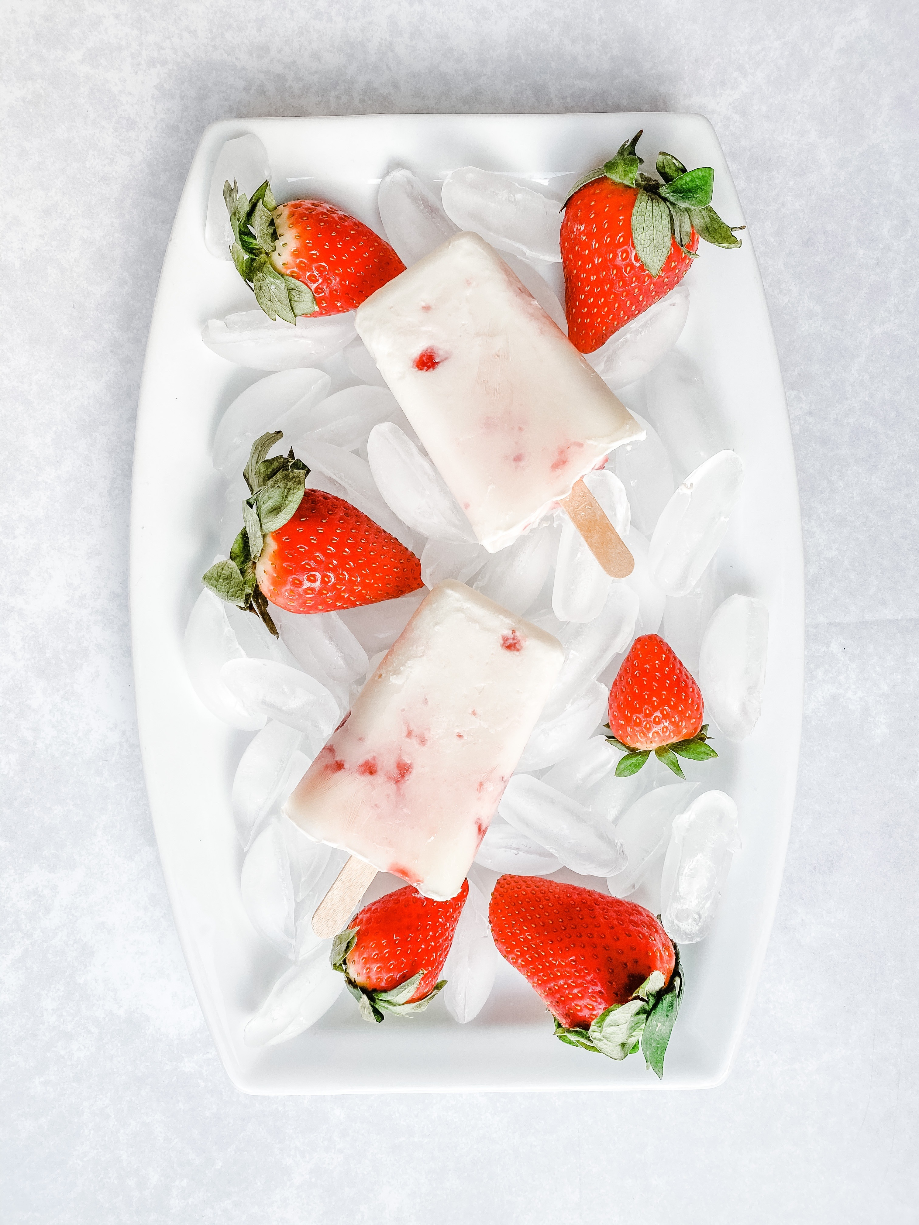 Two yoghurt and jam homemade ice lollies lie on some ice in a white dish and are surrounded by strawberries