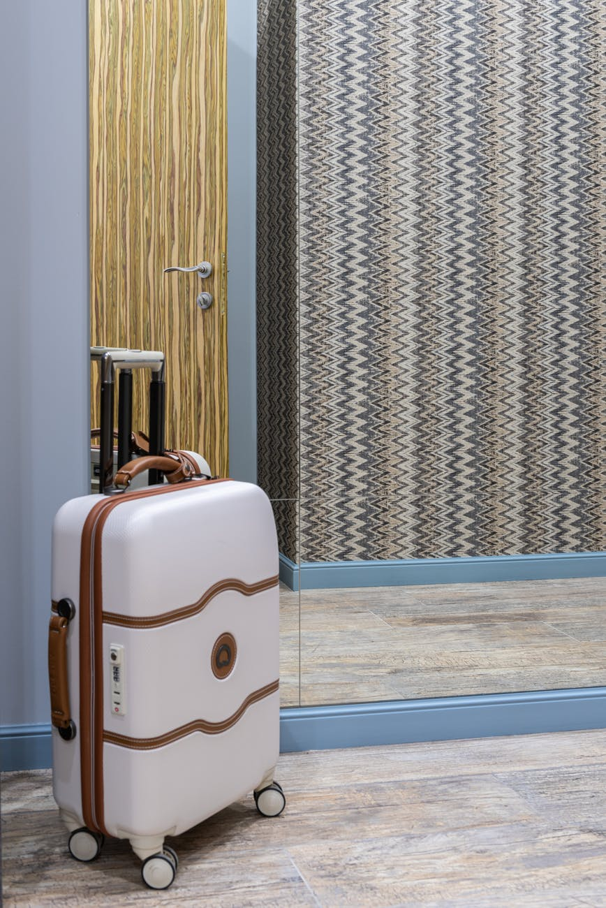 suitcase placed near mirror in room