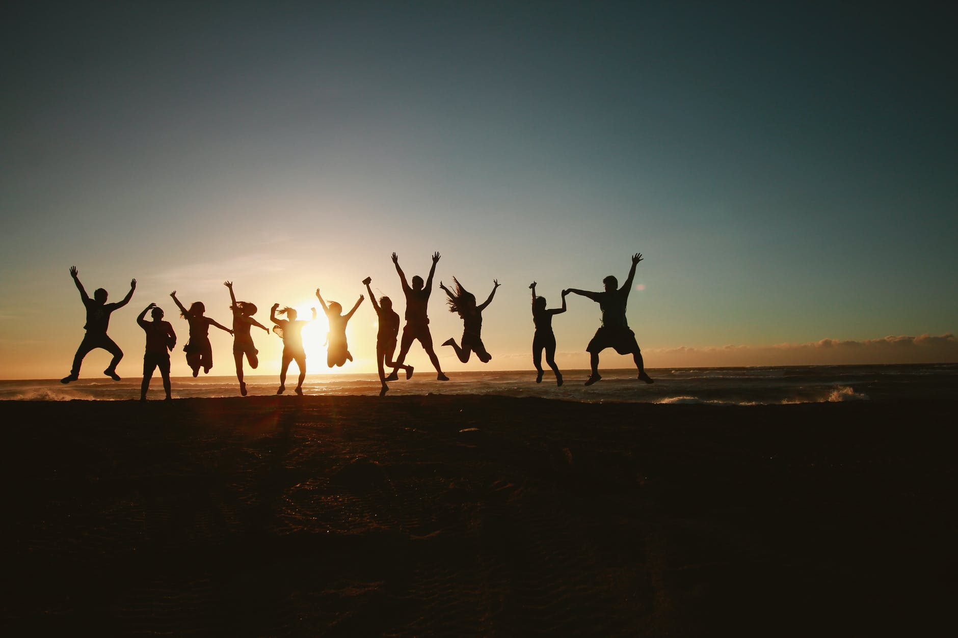 how travel affects your personality silhouette photography of group of people jumping during golden time
