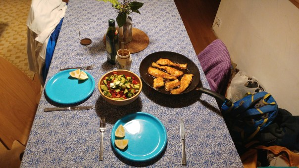 photo of table set with salad and salmon in a pan