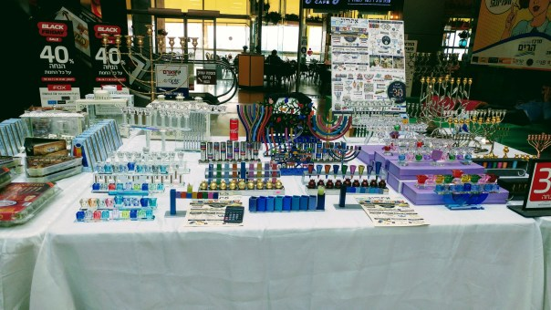 photo of table with a display of many chanukiyot of different colors and designs