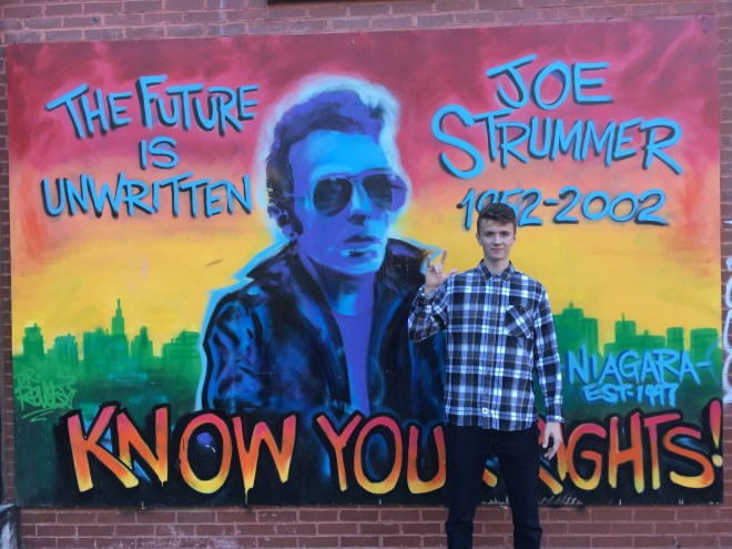 Riley in East Village in front of Punk Rock mural