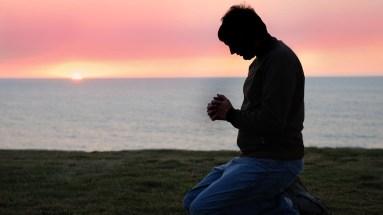 Man praying to God on his knees