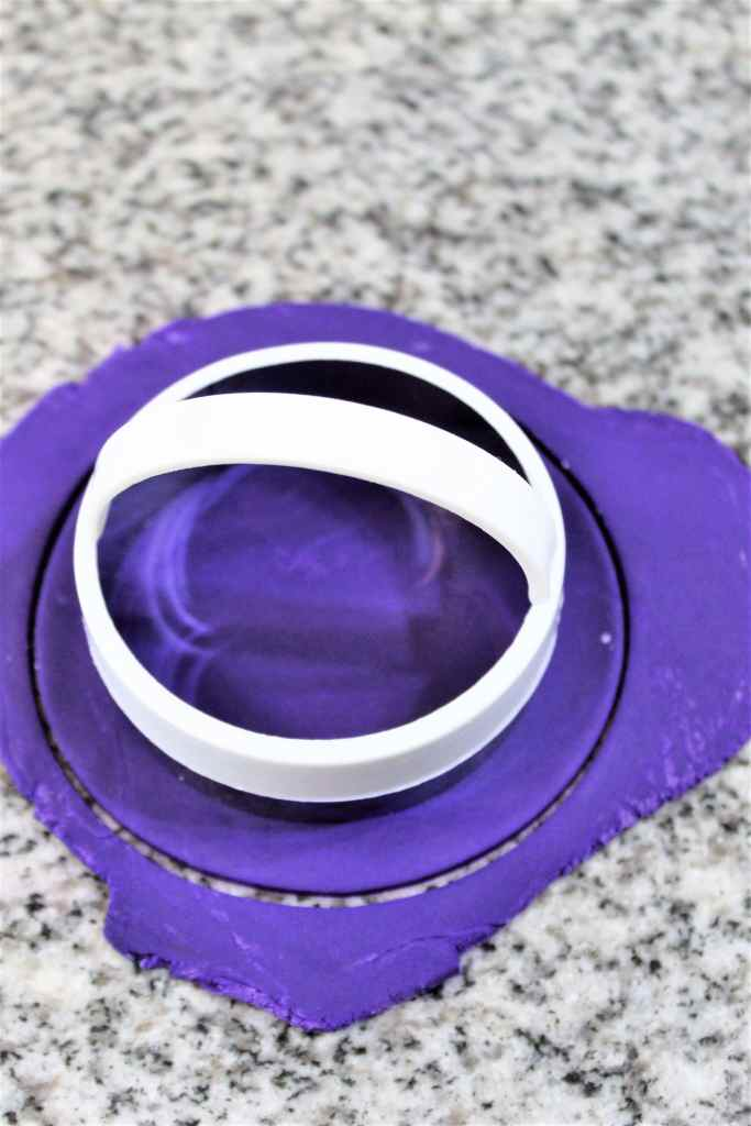 smaller biscuit cutter cutting out purple fondant