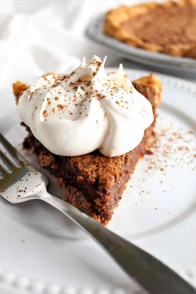piece of chocolate chess pie with whipped cream on a plate with a fork